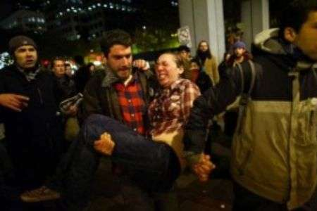 Jennifer Fox being carried by a protester after being hit in the abdomen