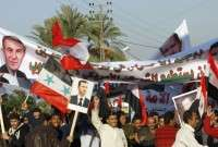 Syrian workers hold pictures of President Bashar al-Assad during a pro-regime rally in the village of Al-Aqibiya near Sidon in Southern Lebanon