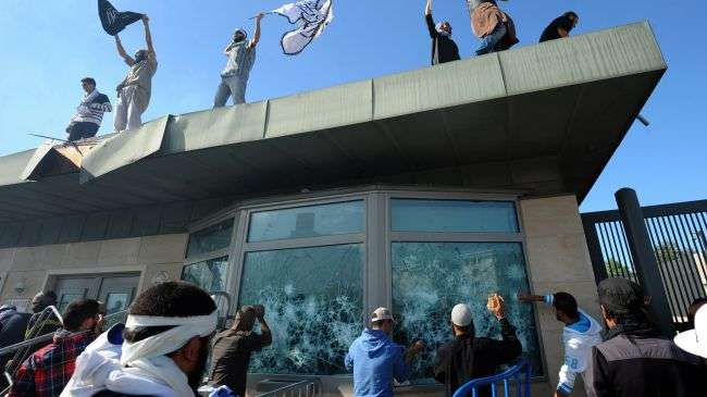 Tunisian protesters break the windows as they hold Islamic flags above the gate of US embassy in Tunis during a protest against the US-made anti-Islam film on September 14, 2012.