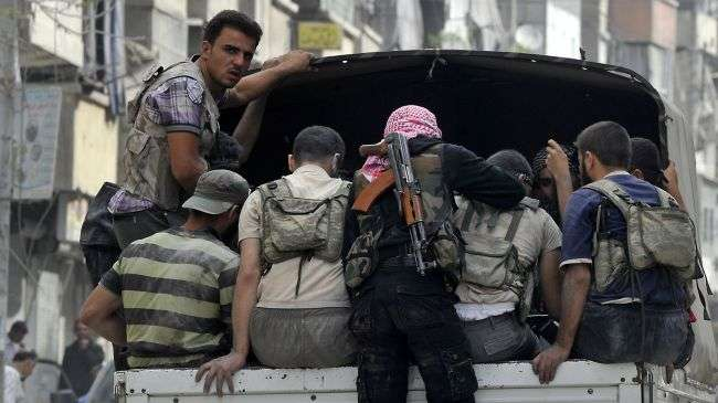 Syrian militants ride on a pick-up truck through a neighborhood the northern city of Aleppo.