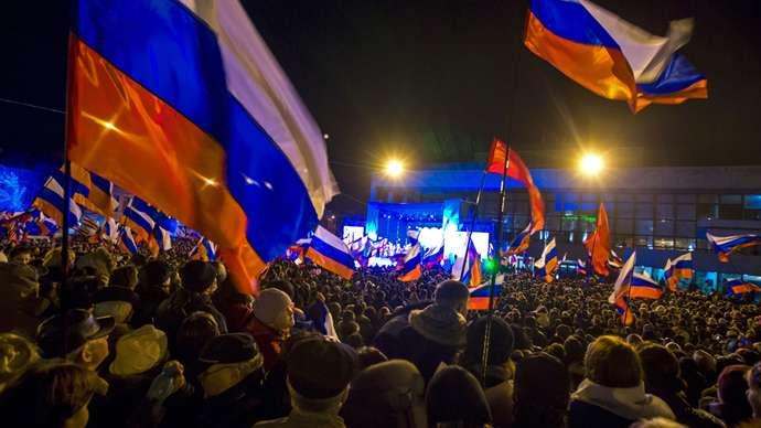 Rakyat merayakan kemenangan saat mereka menunggu pengumuman hasil awal referendum hari ini di Lenin Square di ibukota Krimea Simferopol 16 Maret 2014 (Reuters / Thomas Peter)