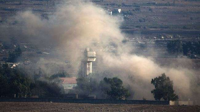 Smoke rises from a village in the occupied Golan Heights following an explosion during fighting between Syrian soldiers and militants near the Quneitra border crossing on August 31, 2014.