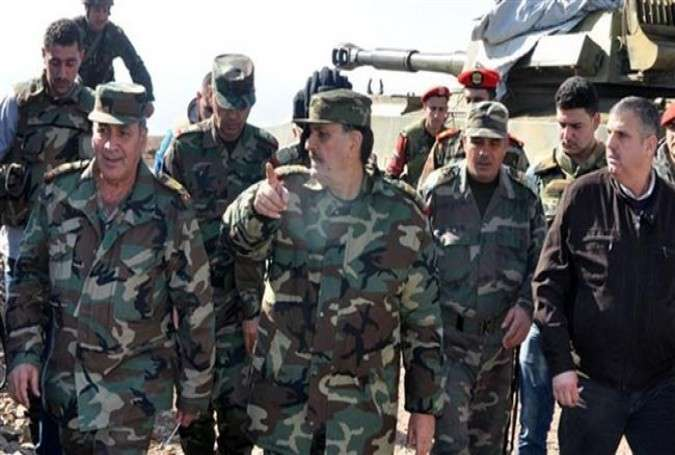 Syria's Defense Minister Fahd Jassem al-Freij (C) is seen along with other syrian military officials checking the readiness of Syrian armed forces in the southern regions of the country, January 22, 2014.