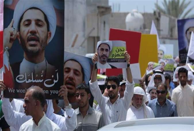 Bahraini protesters hold placards portraying Sheikh Ali Salman, the head of the opposition bloc al-Wefaq National Islamic Society, during a demonstration against his arrest in the village of Diraz, Bahrain, May 22, 2015.