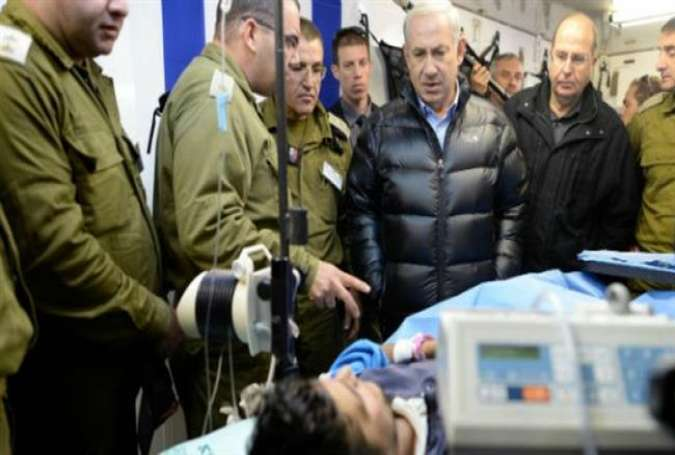 Israeli Prime Minister Benjamin Netanyahu visits a militant wounded in Syria at a field hospital in northern Israel, February 18, 2014.