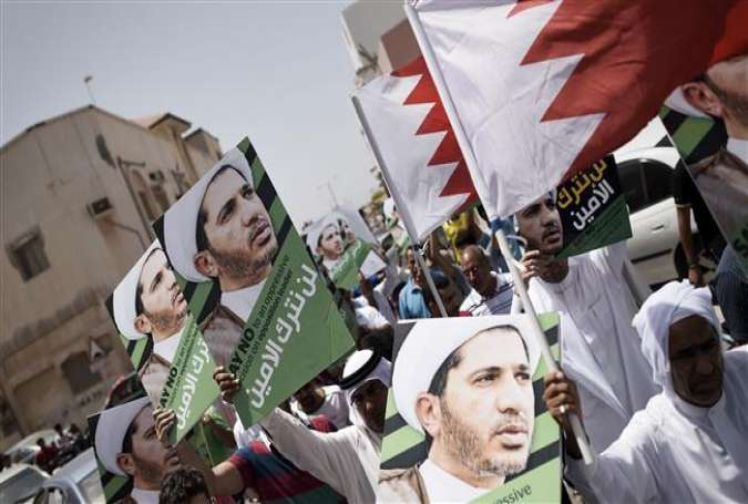 Bahraini protesters hold their national flag and placards portraying Sheikh Ali Salman, the secretary general of Bahrain's main opposition party, al-Wefaq, on June 12, 2015.