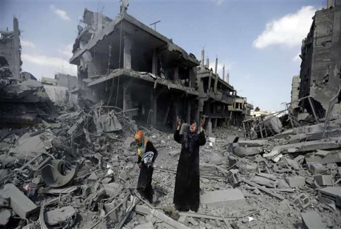 A Palestinian woman pauses amid destroyed buildings in the northern district of Beit Hanoun in the Gaza Strip on July 26, 2014