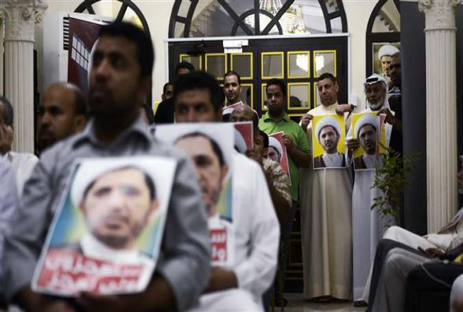 Bahraini men hold placards bearing the portrait of Sheikh Ali Salman, head of the opposition movement Al-Wefaq, during a protest against his arrest on September 14, 2015, in the village of Zinj on the outskirts of the capital, Manama.