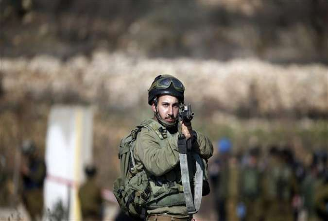 An Israeli soldier points his weapon towards journalists after a Palestinian allegedly attempted to ram his vehicle into the troops at a military checkpoint on December 11, 2015 in the West Bank village of Halhul.