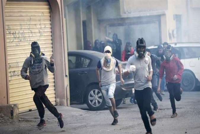 Bahraini protesters run for cover during clashes with police in the village of Sitra, south of the capital, Manama, January 8, 2016.
