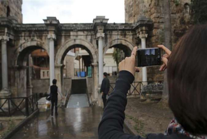 A tourist takes a picture of the Hadrian