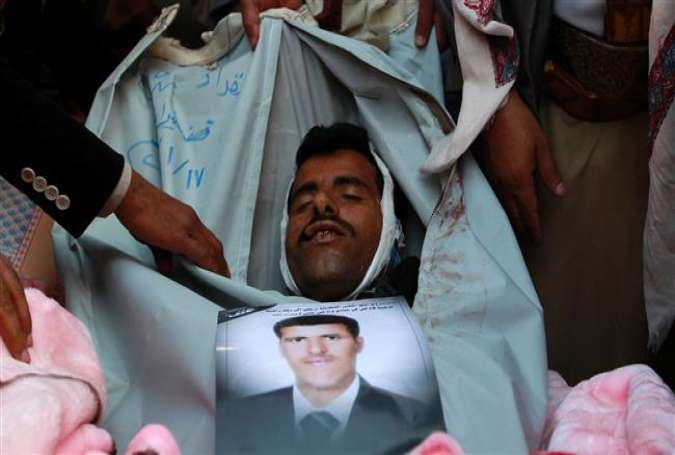 People pray over the body of Almigdad Mojalli, a freelance Yemeni journalist who was killed in a Saudi airstrike, during his funeral on the outskirts of Sana'a on January 18, 2016.