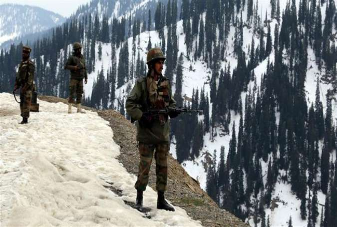 Indian soldiers stand near the site of a gun battle with militants in the Tanghdar sector, north of Kashmir