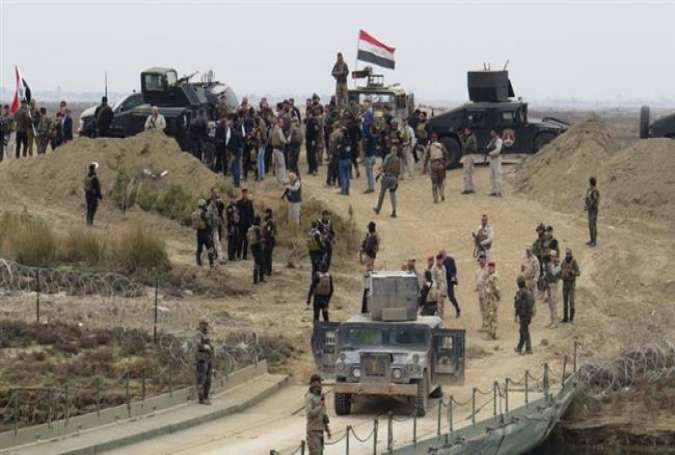 Iraqi security forces gather near a temporary bridge south of Ramadi, Anbar Province, during a visit by Prime Minister Haider al-Abadi, December 29, 2015.