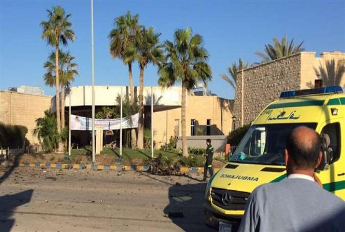 A man stands next to an ambulance outside the Swiss Inn hotel in the Egyptian town of el-Arish, in the Sinai peninsula, following an attack on the hotel by two bombers and a gunman on November 24, 2015.