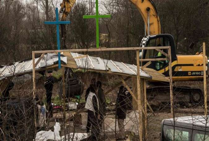 French police stand guard as an excavator knocks down a makeshift mosque and church in a migrant camp in Calais, Feb. 1, 2016.