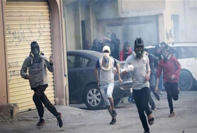 Bahraini protesters run for cover during clashes with police in the village of Sitra, Jan. 8, 2016.