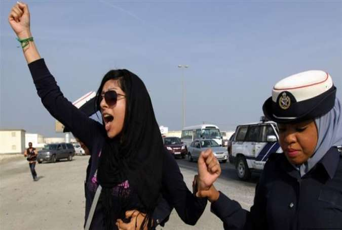 "Bahraini female rights activist, Zainab al-Khawaja (L), gestures as she shouts ""God is greater than any tyrant,"" while being arrested by police officers in Bahrain."