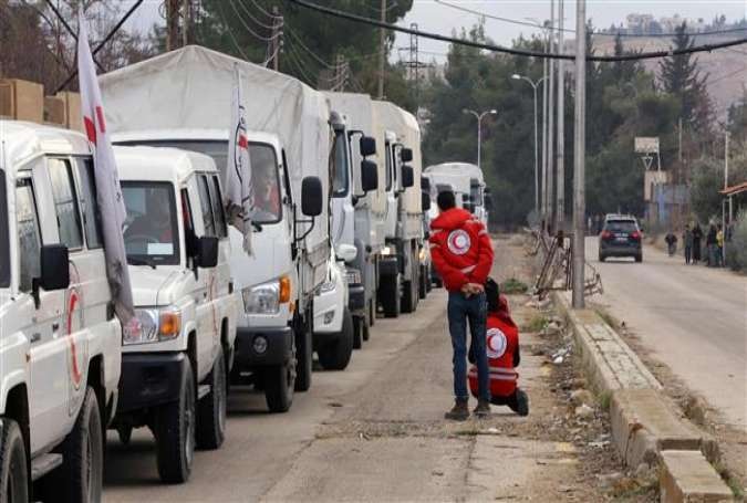 A convoy of aid from the International Committee of the Red Cross (ICRC) waits on the outskirts of the Syrian town of Madaya, on January 11, 2016.