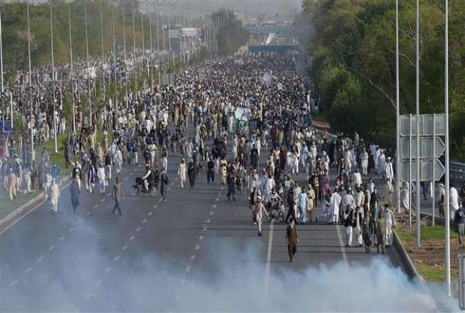 The supporters of Mumtaz Qadri, who has been executed by the Pakistani government for assassinating an outspoken governor, walk as tear gas is fired by police during an anti-government protest in the Pakistani capital, Islamabad, March 27, 2016.