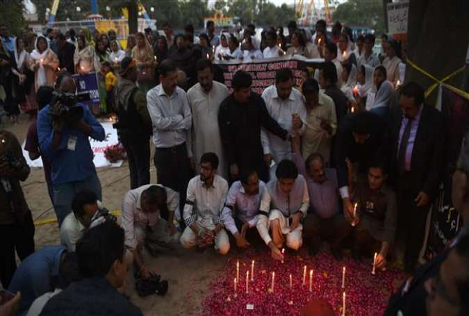 Pakistani civil society members light candles for suicide blast victims in Lahore on March 28, 2016.