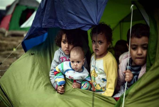 Children sit in a tent in the makeshift camp at the Greek-Macedonian border near the village of Idomeni, where thousands of asylum seekers and refugees are stranded on March 7, 2016.