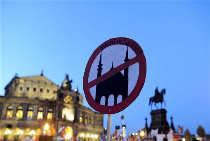 "A supporter of the PEGIDA movement, ""Patriotische Europaeer gegen die Islamisierung des Abendlandes,"" which translates to ""Patriotic Europeans Against the Islamification of the Occident"" holds a poster featuring a crossed sign on a mosque at a protest rally on October 12, 2015."