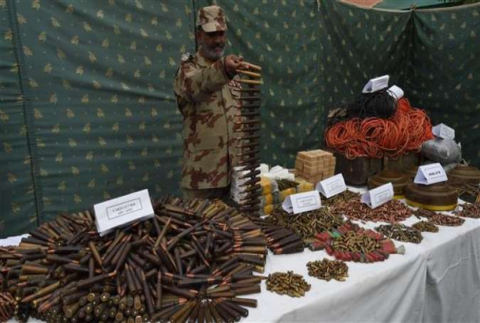 A Pakistani paramilitary soldier poses with a display of seized weapons and ammunition as they are shown to media in Quetta on April 15, 2016.