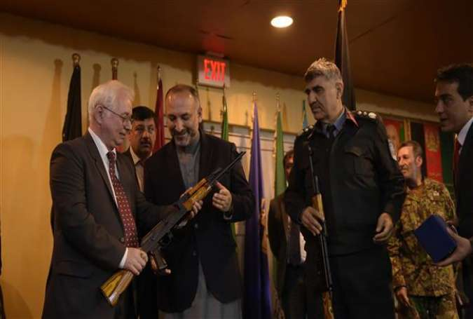 Russian Ambassador to Afghanistan Alexander Mantytskiy (L) hands over an AK-47 rifle to Afghan National Security Adviser Hanif Atmar (center L) during a ceremony at a military airfield in Kabul on February 24, 2016.