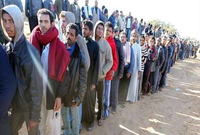 Egyptian refugees from Libya queue for food at a military field hospital on the border.