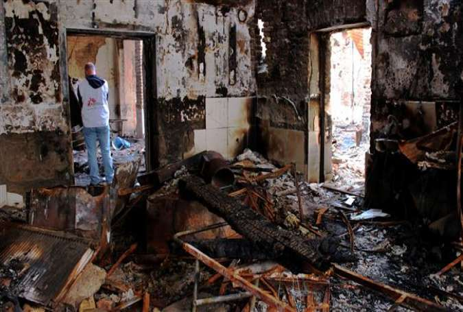 MSF staff as they walk in a damaged hospital which was run by the charity organization in Kunduz, northern Afghanistan.