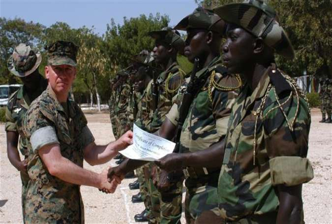 A Senegalese soldier accepts a certificate of completion from a US Marine at a military camp in the African country.