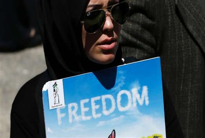 A Palestinian woman holds a poster during a rally demanding the release of the Palestinians held in Israeli jails as people mark the Palestinian Prisoners' Day, April 17, 2016.