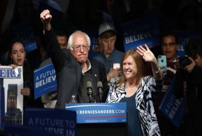 Sen. Bernie Sanders pumps his fist in the air after his wife, Jane, joins him at a campaign event in Louisville, Kentucky, Tuesday night.