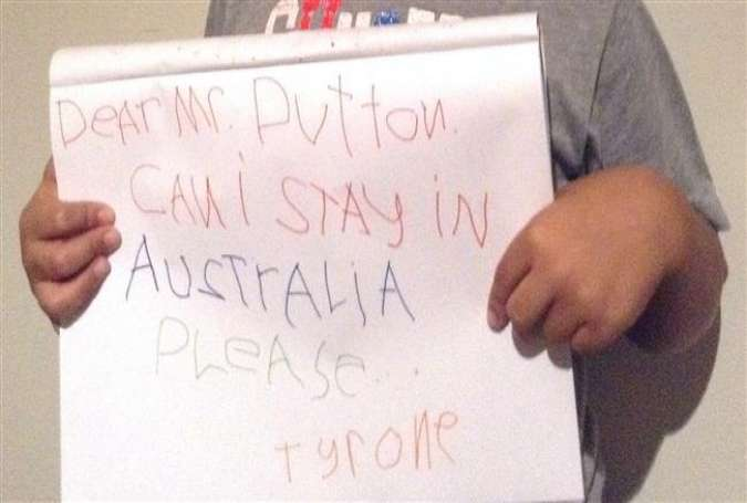 An undated photo received by AFP on April 27, 2015 shows the son of an asylum seeker (unseen) holding a sign he wrote with a message for Australia