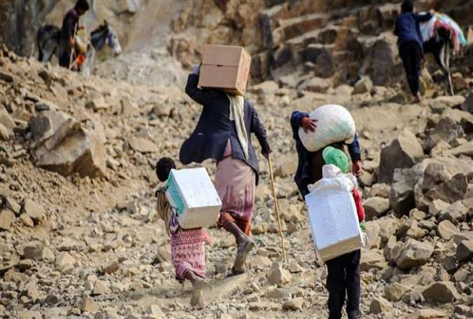 Yemenis carry food parcels as they walk through the mountains between the southern cities of Aden and Ta'izz on December 26, 2015.