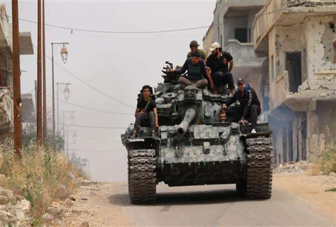 Militants drive a tank in a militant-held area of the southern Syrian city of Dara