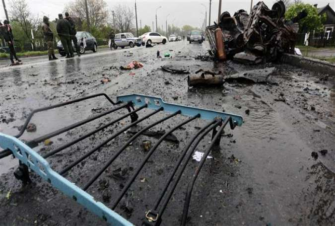Experts examine the site next to a car destroyed by shelling at a checkpoint in Olenivka, small village in the east of Ukraine, on April 27, 2016.