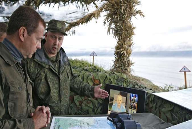 Russian Prime Minister Dmitry Medvedev (L) visits a machine gun regiment on Iturup island, one of four islands in a chain that lies off Russia.