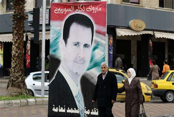 Syrians walk past a portrait of President Bashar al-Assad in the capital Damascus on March 15, 2016.