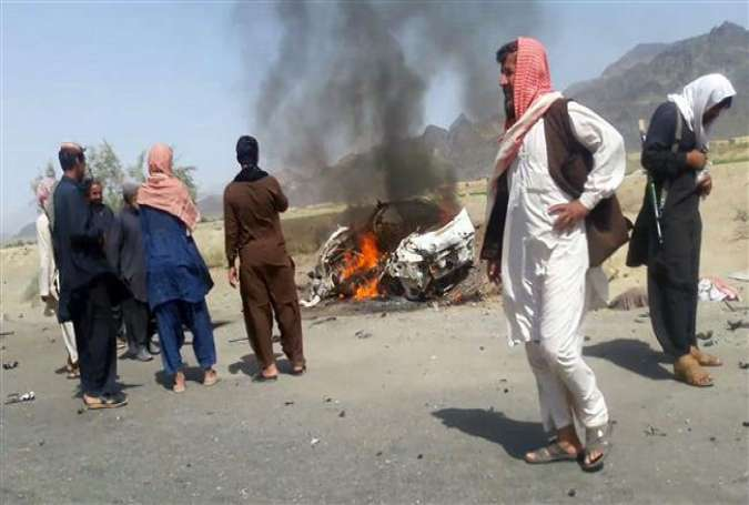 Pakistani local residents gathering around a destroyed vehicle hit by a drone strike in which Afghan Taliban Chief Mullah Akhtar Mansour was believed to be traveling in the remote town of Ahmad Wal in Balochistan.