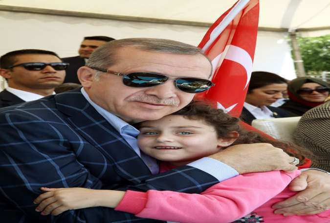 Erdogan hugging a child during a ceremony in Diyarbakir on May 28, 2016.