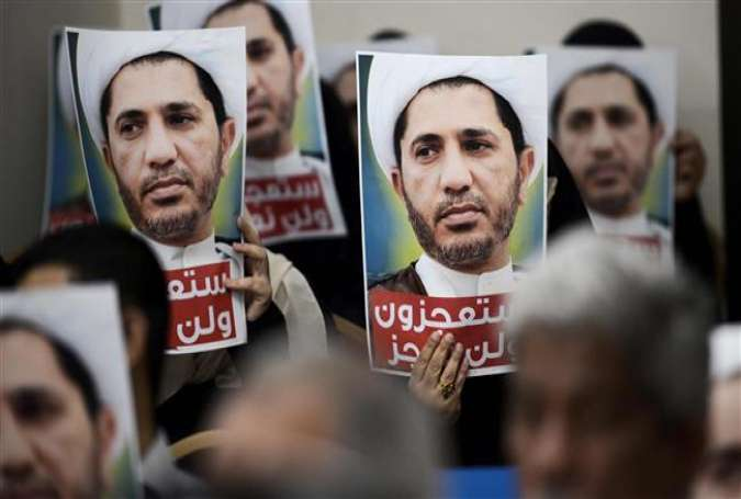 Bahrainis hold placards bearing the portrait of Sheikh Ali Salman, head of the Shia opposition movement Al-Wefaq, during a protest on May 29, 2016 against his arrest, at Wefaq headquarters, in Zinj on the outskirts of Manama.