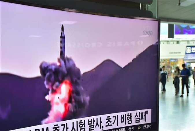 People walk past a television screen at a railway station in Seoul, South Korea, on July 9, 2016, showing file footage of a North Korean missile launch.