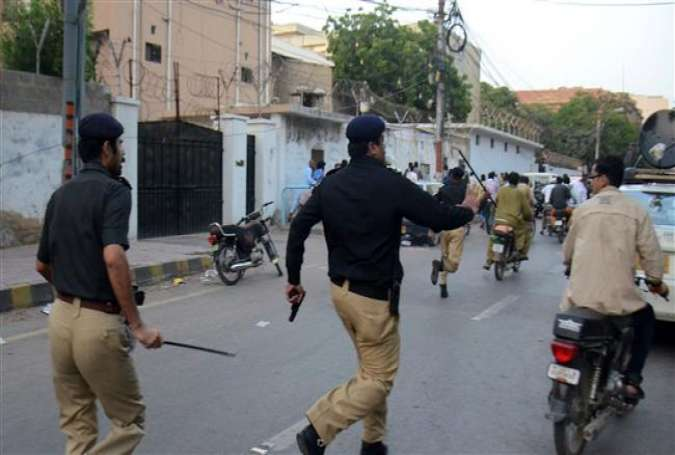 Pakistani policemen chase activists from the Muttahida Qaumi Movement (MQM) politicial party during a clash in Karachi on August 22, 2016. Activists of a key political party clashed with police and ransacked a private television station in the southern Pakistani port city of Karachi on August 22, leaving at least one man dead and seven others injured.