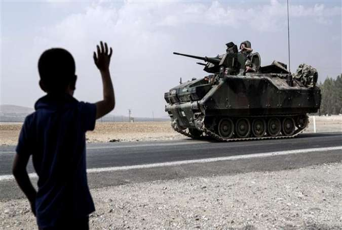 A child waves toward Turkish troops heading to the Syrian border, in Karkamis, Turkey August 26, 2016.