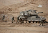 Israeli soldiers run next to a tank in the Negev desert on June 7, 2016.