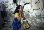 A Palestinian girl reacts at the scene of an explosion that killed eight children