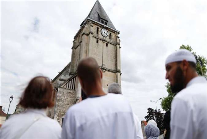 Muslims put flowers and hold a minute of silence on July 29, 2016 in front of the church of Saint-Etienne-du-Rouvray, western France, where a priest was killed on July 26 during a hostage-taking claimed by Daesh Takfiri group.