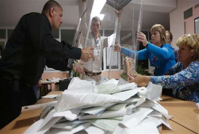 Members of the election commission empty a ballot box at a polling station after Russia